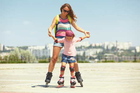 family activities: Young mother with her 5 years old daughter rollerskating in park Stock Photo