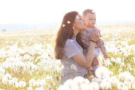 Moeder en haar kind spelen in het voorjaar veld in zachte zonlicht