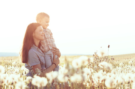 toddler walking: Mother and her child playing in spring field in soft sunlight
