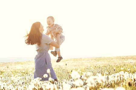 sunlight: Mother and her child playing in spring field in soft sunlight