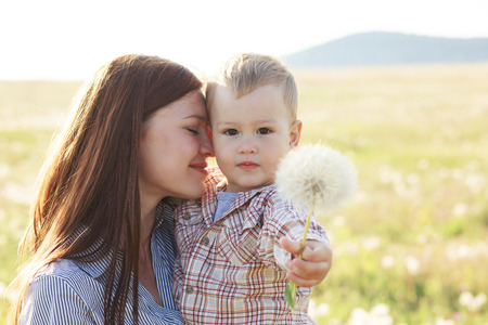summer  sunlight: Mother and her child playing in spring field in soft sunlight