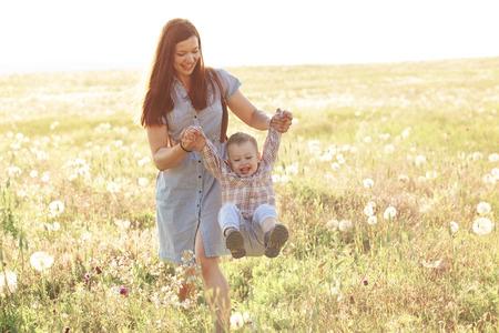 mama e hijo: Madre y su hijo jugando en el jardín de primavera en la luz del sol suave