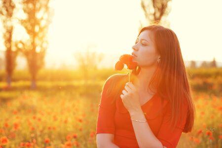 woman in field: Young woman smelling flower in sunlight in poppy field