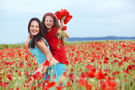 preteen: Mother and her 7 years old preteen child playing in spring flower field