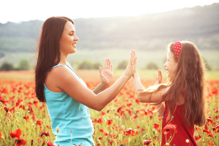 preteen: Mother and her 7 years old preteen child playing in spring poppy field in soft sunlight