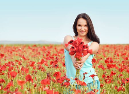 woman in field: Young woman enjoying nature in spring poppy field Stock Photo