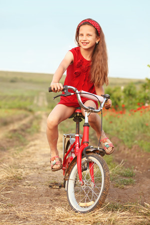 preteen girl: Preteen girl on bicycle in spring field Stock Photo