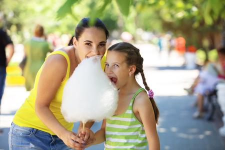 algodon de azucar: El niño come el caramelo de algodón con la mama en calle de la ciudad