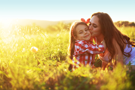 6 years: Mom and her 6 years old child playing in spring field. Mother kissing daughter.