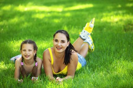 niños sentados: Madre joven con sus 6 años de edad del niño rollerskating en parque
