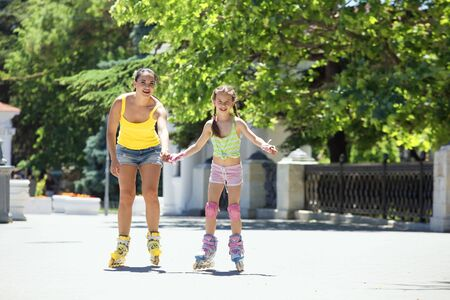 rollerskating: Young mom with her 6 years old child rollerskating in park Stock Photo