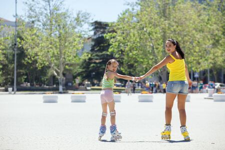 two year old: Young mom with her 6 years old child rollerskating in the city street