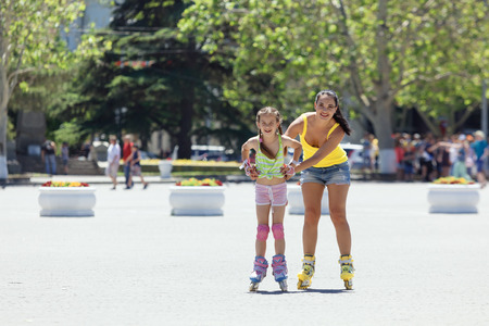 rollerskating: Young mom with her 6 years old child rollerskating in the city street