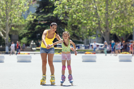 woman street: Young mom with her 6 years old child rollerskating in the city street