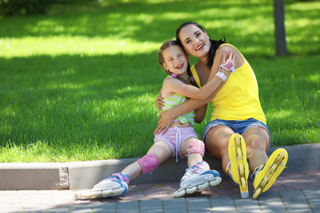 rollerblading: Young mom with her 6 years old child rollerskating in park Stock Photo
