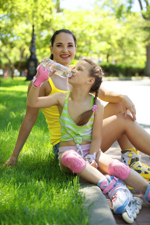 6 years: Young mom with her 6 years old child rollerskating in park Stock Photo