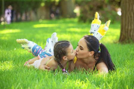 girls kissing girls: Young mom with her 6 years old child rollerskating in park. Daughter kissing mother. Stock Photo