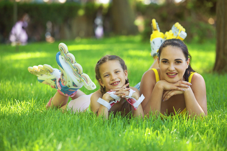 healthy family: Young mom with her 6 years old child rollerskating in park Stock Photo