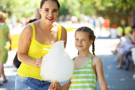 Child eats cotton candy with mom in city street photo