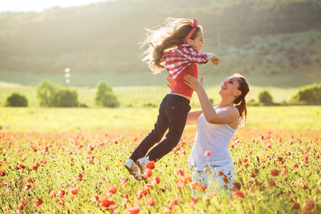 children walking: Mom and her 6 years old child playing in spring flower field