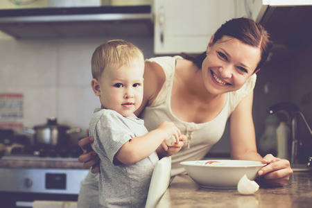 women children: Mom with her 2 years old child cooking holiday pie in the kitchen to Mothers day, casual lifestyle photo series in real life interior Stock Photo