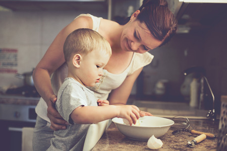 mother: Mom with her 2 years old child cooking holiday pie in the kitchen to Mothers day, casual lifestyle photo series in real life interior Stock Photo