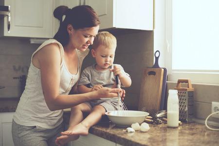 haciendo el amor: Mam� con sus 2 a�os de edad cocinar ni�o pastel de fiesta en la cocina para el d�a de madres, la serie del estilo de vida foto ocasional en el interior de la vida real Foto de archivo