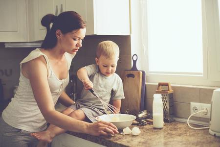 cocina antigua: Mamá con sus 2 años de edad cocinar niño pastel de fiesta en la cocina para el día de madres, la serie del estilo de vida foto ocasional en el interior de la vida real Foto de archivo