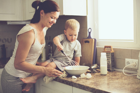 Mom with her 2 years old child cooking holiday pie in the kitchen to Mothers day, casual lifestyle photo series in real life interior Standard-Bild