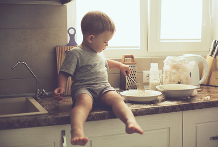 2 persons only: 2 years old child cooking alone in the kitchen, casual lifestyle photo series in real life interior