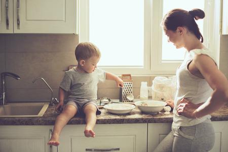 Moeder met haar 2 jaar oude kind koken vakantie taart in de keuken om de dag van Moeders, casual lifestyle fotoserie in het echte leven interieur Stockfoto
