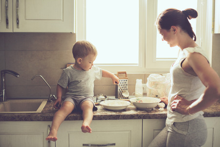 home cooking: Mom with her 2 years old child cooking holiday pie in the kitchen to Mothers day, casual lifestyle photo series in real life interior Stock Photo
