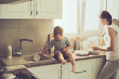 乳幼児: 料理休日円母の日にキッチンで, 実際の生活のインテリアでカジュアルなライフ スタイル写真シリーズ彼女の 2 歳の子を持つお母さん 写真素材