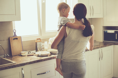 Mom with her 2 years old child cooking holiday pie in the kitchen to Mothers day, casual lifestyle photo series in real life interior Stock fotó
