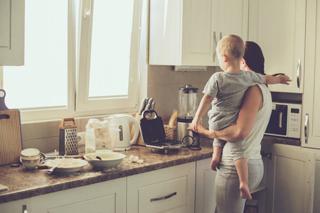 mother cooking: Mom with her 2 years old child cooking holiday pie in the kitchen to Mothers day, casual lifestyle photo series in real life interior Stock Photo