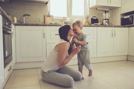 mama e hijo: Mamá con sus 2 años de edad cocinar niño pastel de fiesta en la cocina para el día de madres, la serie del estilo de vida foto ocasional en el interior de la vida real Foto de archivo
