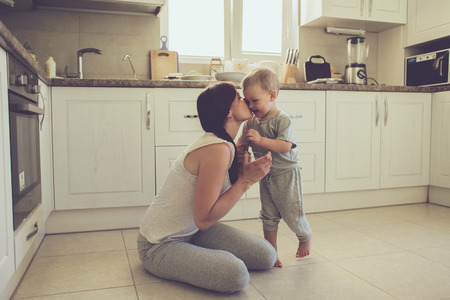 women kissing: Mom with her 2 years old child cooking holiday pie in the kitchen to Mothers day, casual lifestyle photo series in real life interior Stock Photo