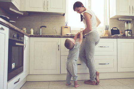 Mom with her 2 years old child cooking holiday pie in the kitchen to Mothers day, casual lifestyle photo series in real life interior Stockfoto