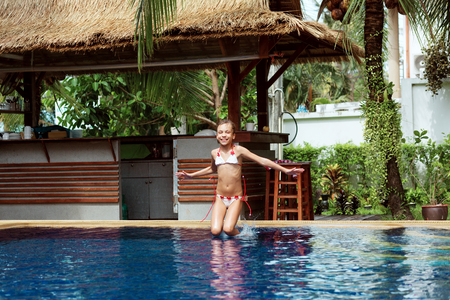 8 years old girl playing in swimming pool at hotel