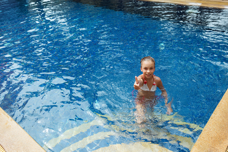 8 years old: 8 years old girl playing in swimming pool at hotel