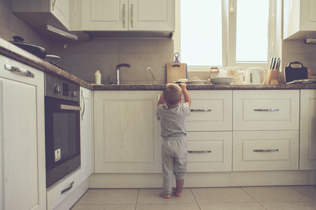 2 years old child standing on the floor alone in the kitchen, casual lifestyle photo series in real life interior Standard-Bild