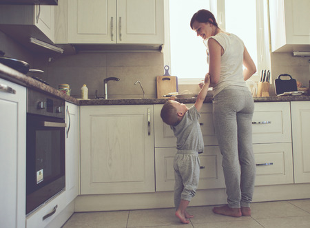Mom with her 2 years old child cooking holiday pie in the kitchen to Mothers day, casual lifestyle photo series in real life interior photo