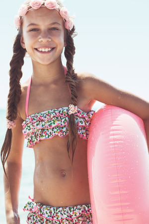 9 years old girl dressed in fashion floral swimsuit posing with inflatable ring at the beach in sunlight Stock Photo