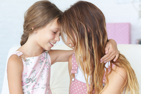 eight year old: Mother with her 8 years old daughter hugging on a sofa at home
