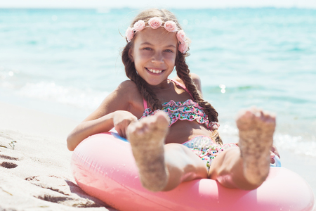 9 years old girl dressed in fashion floral swimsuit playing with inflatable ring at the beach in sunlight Stock Photo