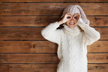 winter fashion: Cute 9 years old girl wearing knitted autumn or winter clothing posing over wooden background Stock Photo