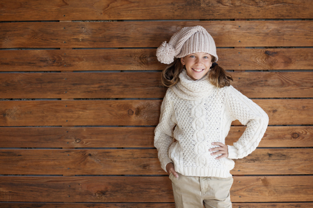 fashion model: Cute 9 years old girl wearing knitted autumn or winter clothing posing over wooden background Stock Photo