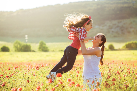 6 years: Mom and her 6 years old child playing in spring flower field