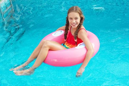 schwimmring: 9 Jahre Kind beim Spielen im Schwimmbad auf aufblasbaren Ring