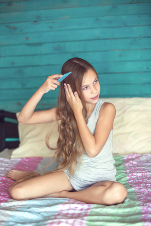 nine years old: 9 years old girl brushing her long hair in her bedroom in the morning
